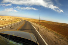 Car on remote highway. Bonnet or hood of motor car traveling on remote highway with blue sky and cloudscape background Stock Photography
