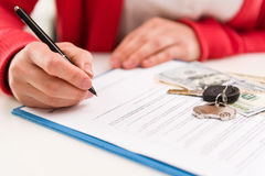 Car rent and sale. Closeup of woman auto dealer signing rental contract in the office. Car key and money on papers. Shallow depth of field Royalty Free Stock Photography