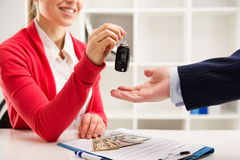 Car rent and sale. Rental contract. Transport purchase. Woman automotive dealer offering car key to buyer. Shallow depth of field Stock Image