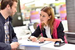 Car rental assistant informing client. Car rental assistant giving information to customer royalty free stock images