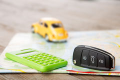 Car rental concept - car key and calculator on the map Royalty Free Stock Images