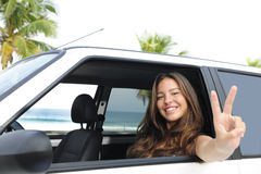 Car rental: happy woman in her car near the beach Stock Photos