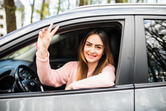 Car rental happy woman in her car near the beach showing victory sign Stock Images