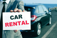 Car rental. A man in suit holding a signboard with the text car rental written in it and a car in the background royalty free stock image