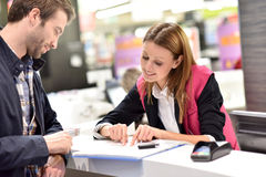 Car rental saleswoman with client. Car rental assistant giving information to customer royalty free stock photography