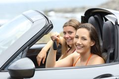 Car renters holding a key looking at you. On vacations royalty free stock image