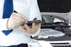 Car repair. Technician writing on a clipboard standing in front of a car at work Royalty Free Stock Images