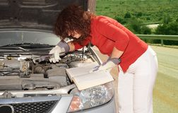Car Repair. The Elderly Woman At The Car With Lifted Cowl Royalty Free Stock Image