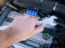 Car repair. Tool in the hand of man to repair the car Stock Photo