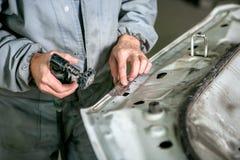 Car repair in car service. Locksmith grinds car detail, hands close-up stock image