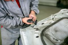 Car repair in car service. Locksmith grinds car detail, hands close-up stock image