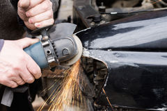 Car repair after crash. Repair service worker fix damaged car after crash on the road. Working with angle grinder to fix metal body Royalty Free Stock Photos