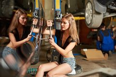 Car repair performed by a girl with a spanner in her hands Royalty Free Stock Image