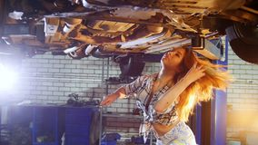 Car repair service. A car lift. Young woman standing under the car. Solves the problem stock video
