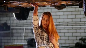 Car repair service. A car lift. Young woman walks under the car and linger hanging upon it. Looking in the camera stock video