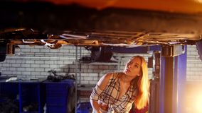 Car repair service. A car lift. Young woman standing under the car. Solves the problem with a wrench stock footage