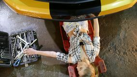 Car repair service. Young woman coming out of the bottom of the car, takes a wrench and comes back to work stock video