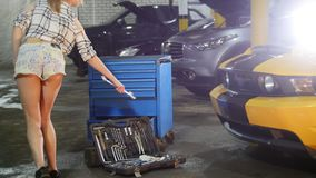 Car repair service. Young woman in small shorts walks to the tool case, bends down and takes the wrench stock video