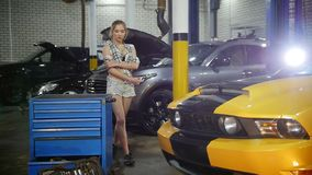 Car repair service. Young woman walks around the servise. Slow motion stock video