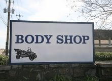 Car Repair Shop. A body shop and automobile collision repair shop sign where cars can be repaired after an accident Stock Photos