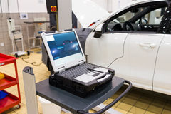 Car Repair Shop. Car in a professional auto repair shop,testing with laptop Stock Images