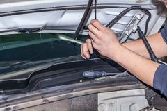A car repairman unscrews parts windscreen wipers with a wrench with a green handle in the engine compartment in a vehicle repair. Workshop stock photos