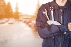 Car repair industry. Car repairman wearing a dark blue uniform standing and holding a wrench that is an essential tool for a mechanic and has a backdrop as a car Royalty Free Stock Photography
