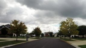 A car ride down road in residential suburban neighborhood looking at trees, clouds, houses and landscape. Car interior driving down road looking out front stock video footage