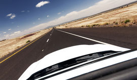 Car ride on road in Nevada desert. White car on an endless road through desert Royalty Free Stock Image