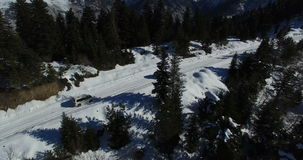 The car rides along a snow-covered road in a coniferous forest. Video from the drone. Dron takes a video car that travels along a snow-covered road among stock footage