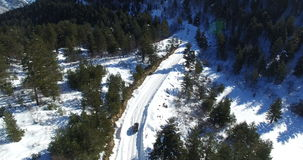 The car rides along the snow-covered road among the mountains. Video from the drone. The aerial photography of the machine that moves down from the mountainside stock video footage
