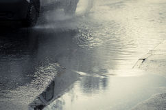 Car rides on big puddle. Water splash. Manchester England. Royalty Free Stock Photo