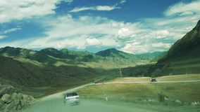 The car rides on a dusty gravel mountain road. Road works ahead stock video
