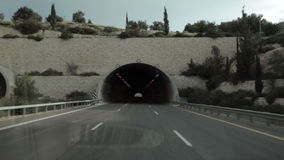 Car rides on the highway road and enters the dark. The car rides on the highway and enters the dark tunnel stock footage