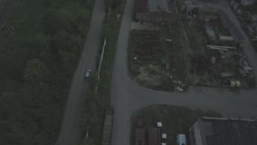 Car rides on the road out of town aerial view. Cars ride by road near fenced construction site at spring sunny day stock video footage