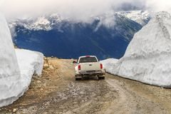 car rides on a wet, stony, dirt, mountain road, between snowdrifts, ahead of the mountain stock image