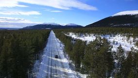The car rides on a winter road among the woods and. Mountains HD stock video footage