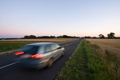 Car on the road. Car driving on the road going towards horizon during sunset Royalty Free Stock Photo