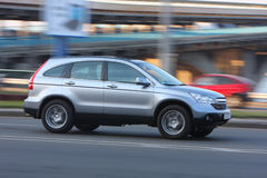 Car on the road. Fast silver 4wd car on the road with bridge on background Stock Photography