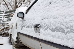 Car after road accident in a parking lot near workshop is covered with snow. Safe driving in winter Royalty Free Stock Photography
