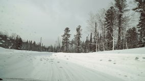 Car road covered by heavy snow in winter day, winter woods stock video