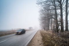 Car on a road in fog Royalty Free Stock Photo
