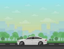 Car on the road with forest and cityscape background Stock Photo