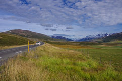Car in the road leading to snow covered mountains Royalty Free Stock Images