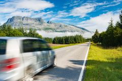 Car on road in Norway, Europe. Auto travel through scandinavia. Blue sky and mountain in background royalty free stock photos