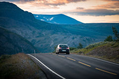 Car on road in Norway, Europe. Sunset travel. Car on country road in Norway, Europe, Scandinavia. Auto travel on sunset. Orange sky with clouds Royalty Free Stock Images