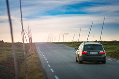 Car on road in Norway, Europe. Sunset travel. Car on country road in Norway, Europe, Scandinavia. Auto travel on sunset. Blue sky with clouds Royalty Free Stock Photo