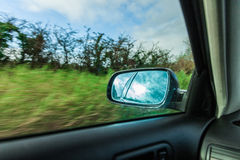 Car on the road and rear view mirror Stock Photos