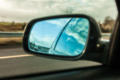 Car on the road and rear view mirror Stock Images