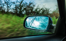 Car on the road and rear view mirror Royalty Free Stock Photo